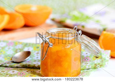 Delicious orange jam. Homemade orange jam in a glass jar, spoon, textile napkin, orange slices on a table. Healthy citrus dessert. Closeup