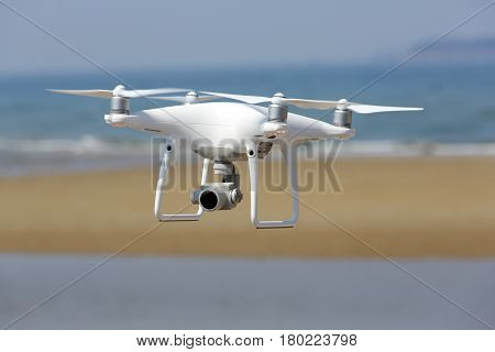 KAGAWA, JAPAN - APRIL 03, 2017: White remote controlled Drone Dji Phantom4 Pro equipped with high resolution video camera hovering in air with shore and blue sky in the background