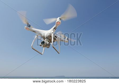 KAGAWA, JAPAN - APRIL 03, 2017: White remote controlled Drone Dji Phantom4 Pro equipped with high resolution video camera hovering in air with shore and blue sky in the background poster
