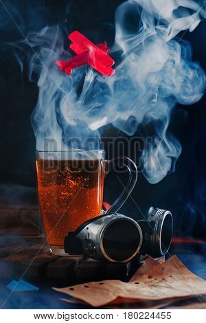 Aviation still life with a glass cup of coffee, goggles, rising cloud of steam and a red handmade airplane