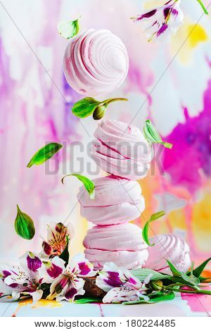 Levitating marshmallow with a pile of pink russian zephyr with spring flowers on a light background