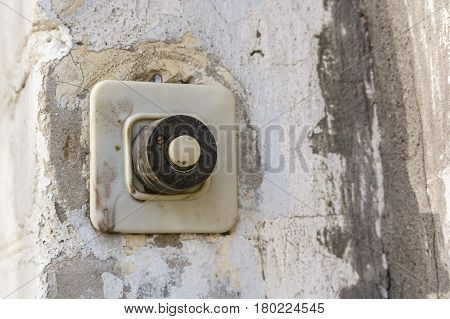 Old plastic door bell button on grunge plaster surface