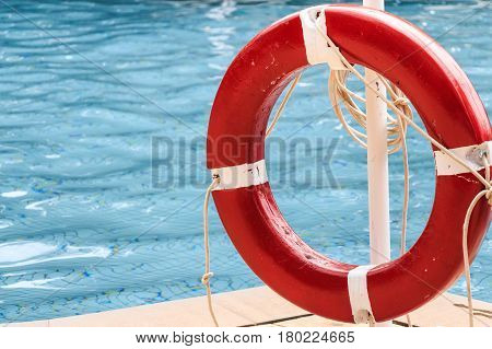 Closeup of red life buoy with blue water in background