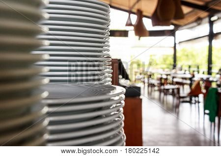 Close up of stack of clean white plates in restaurant