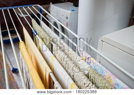 Close up of several colorful towels dry on drying line indoors