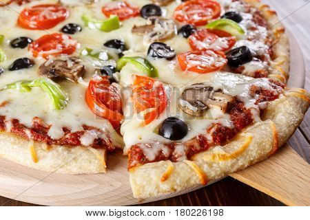 Slice of vegetables and mushrooms pizza and a whole pizza on a cutting board