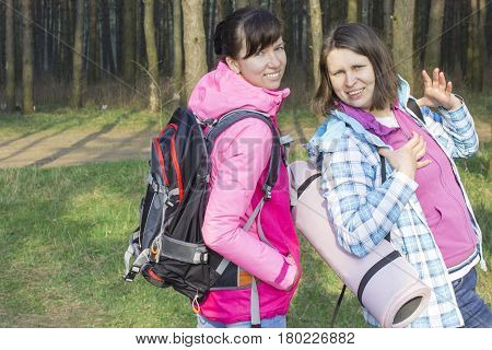 Two young ladies with backpacks walking through green meadow.