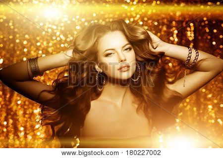Golden beautiful fashion woman, model with shiny  healthy long volume hair. Waves curls updo volume hairstyle. Hair Salon.Girl with luxurious haircut on  gold background