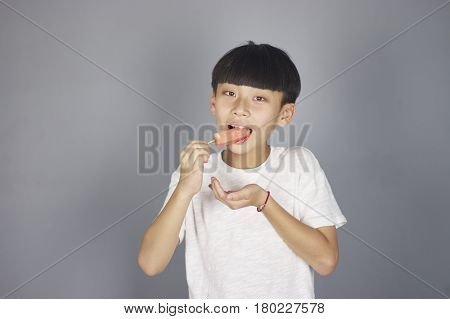 Portrait Of Asian Boy Eating Watermelon In Studio