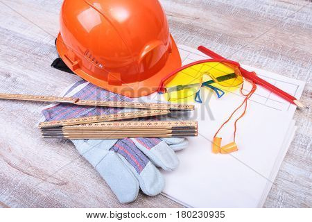 Orange hard hat, Earplug to reduce noise, safety glasses, gloves, pen and measuring tape on wooden background