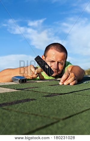 Man fastening bitumen roof shingles with nails and hammer - low angle view focus on hand