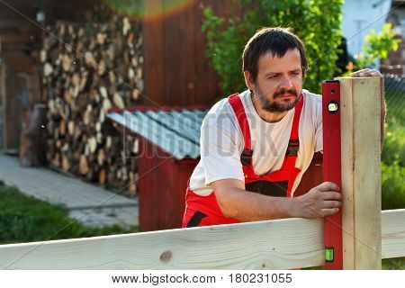 Man building a wooden fence in backyard - checking the posts with a level - backlit worker
