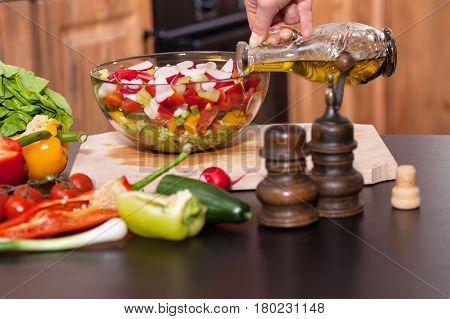 Making a fresh vegetables salad - hand pouring the oil closeup