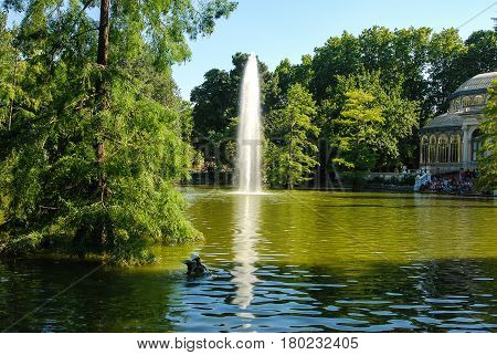 Pond surrounded by trees  with fountain at El Retiro Park in Madrid,Spain,