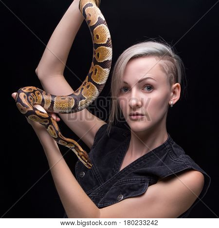 Blond young woman with snake on black background