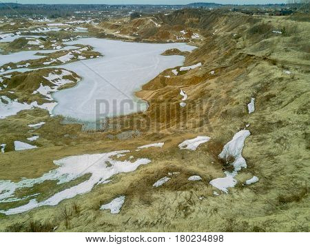 Abandoned sandy quarry in the winter, flooded with water, turned into ice