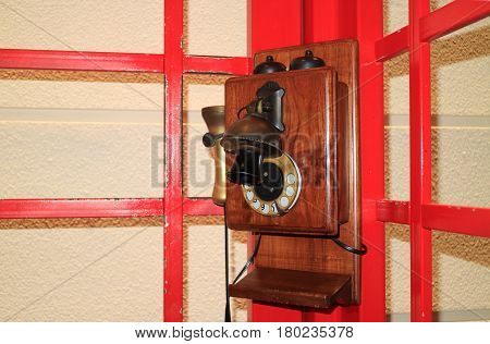 Vintage style wooden public telephone in the red colored telephone booth