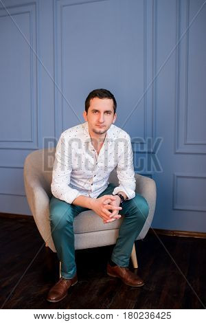 Serious handsome young businessman in white shirt and green trousers sitting in armchair and looking at camera