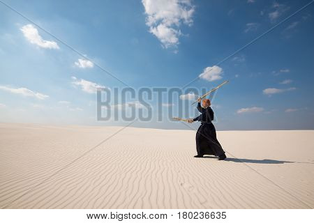 Confident Man Practicing With A Training Sword In Desert