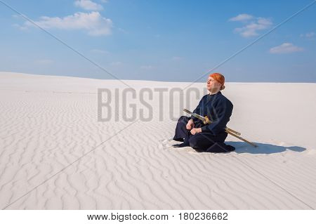 Man In Traditional Clothes Meditates During The Practice Of Martial Arts