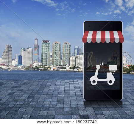 Modern smart mobile phone with on line shopping store graphic and motor bike icon on stone tile floor over office city tower river and blue sky Shop online delivery service concept