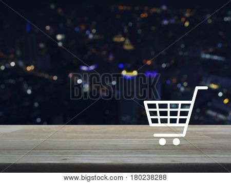 Shopping cart icon on wooden table over blur colourful night light city tower background Shop online concept