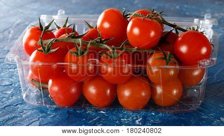 Fresh tomatoes on the vine in plastic packing