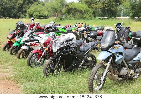 Rows Of Colourful Parked Motorbikes On Green Grass