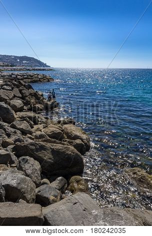 Amazing sea with blue summer wave and rocks. Summer sea background. Endless sea. Daylight sea. Turquoise sea. Sea foam and brown rocks. Sunny day sea with fishermen.