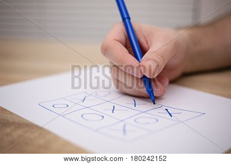 male adult hand holding blue pen above a paper with a tic-tac-toe game