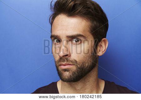 Annoyed guy on blue background portrait studio shot