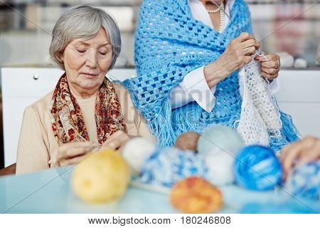 Concentrated elderly woman sitting in comfortable armchair and knitting warm scarf to her granddaughter, her friend with cornflower blue shawl sitting on armrest