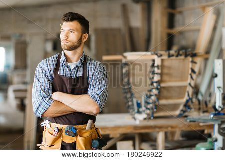 Waist-up portrait of confident bearded carpenter with arms crossed standing in spacious workshop and looking away