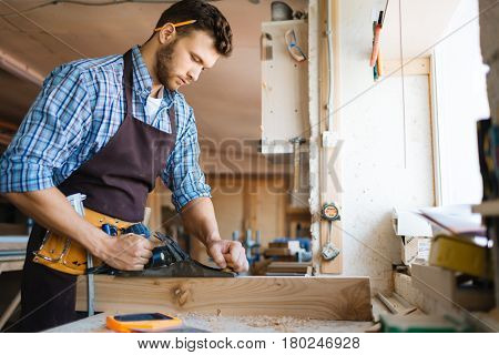 Profile view of confident young carpenter in apron planing board with jointer plane in spacious workshop