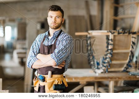 Portrait of serious young woodworker wearing leather tool belt posing for photography while standing in workshop with arms crossed