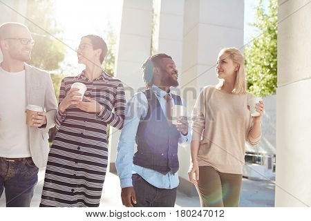 Multiethnic group of joyful financial managers walking together in city center and having small talk during coffee break, lens flare