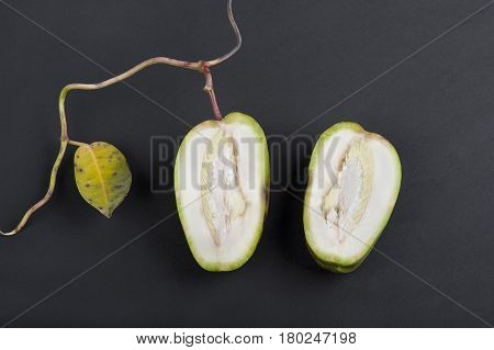 still life of brunch with one leaf and fruit cut in a half on black background, closeup