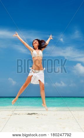 Happy young woman jumping on the beach. White sand, blue sky and crystal sea of tropical beach. Vacation. Ocean beach relax, travel to islands. Happy lifestyle