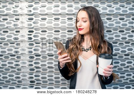 Portrait of a young business woman with phone and coffee to go on the metal wall background