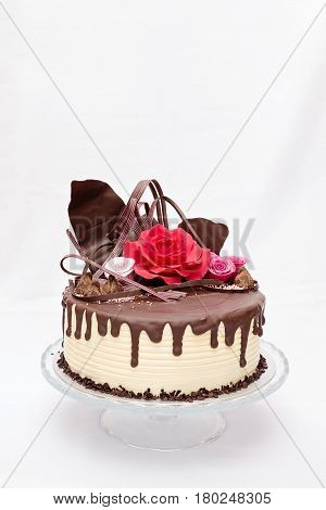Rould one layer white and brown chocolate cake with red and pink edible marzipan flowers on top