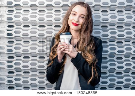 Portrait of a young pretty business woman with coffee to go on the metal wall background