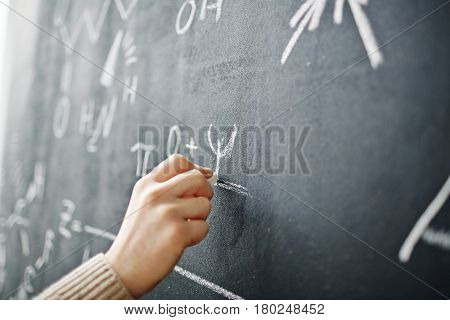 Closeup shot of male hand writing algebraic formula on blackboard with chalk