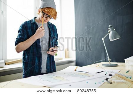 Portrait of young red haired designer wearing glasses and beanie hat working in office: standing at desk with floor plans, thinking and using smartphone