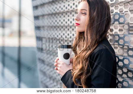 Young caucasian business woman standing with coffee to go outdoors near the modern facade