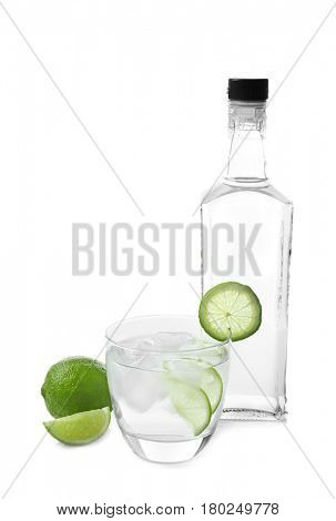 Glass and bottle of tequila on white background