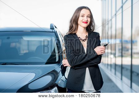 Happy female buyer holding keys near the car in front of the modern avtosalon building