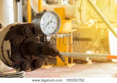 Closeup of pressure gauge pressure gauge measuring gas pressure. Pipes and valves at oil and gas industrial plant.