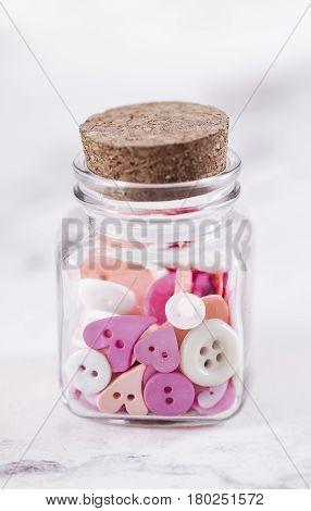 A jar full of pink buttons spilling out on white surface
