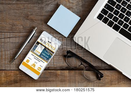 Real estate website in a mobile phone screen. House search concept.