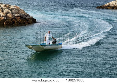 Man in traditional arabic thawb ride a speedboat near a coast in Oman 18.april 2012